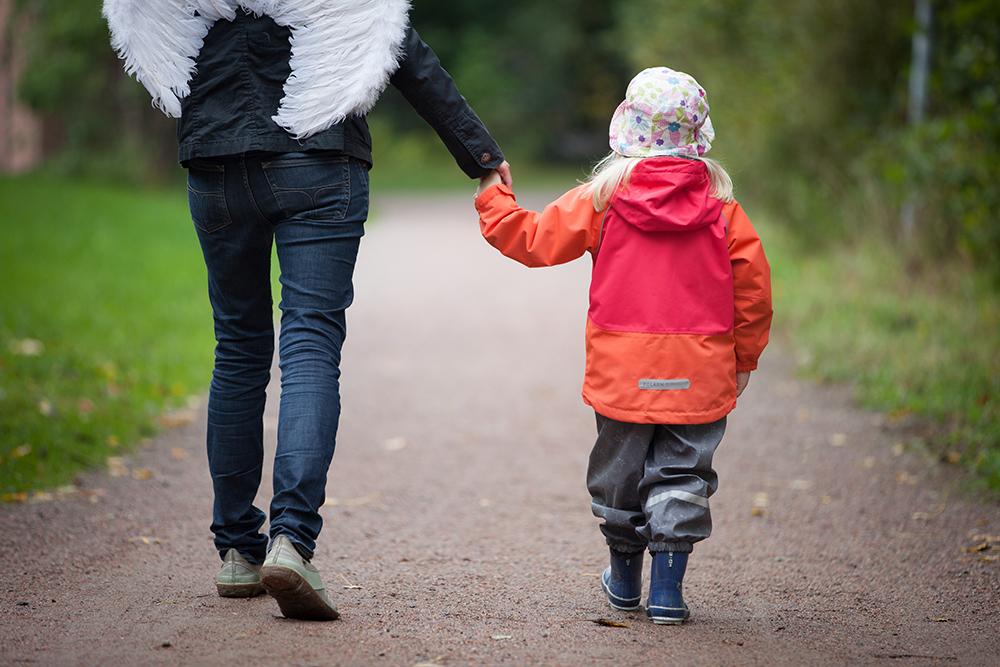 Aikuinen, jolla on enkelinsiivet, taluttaa lasta.