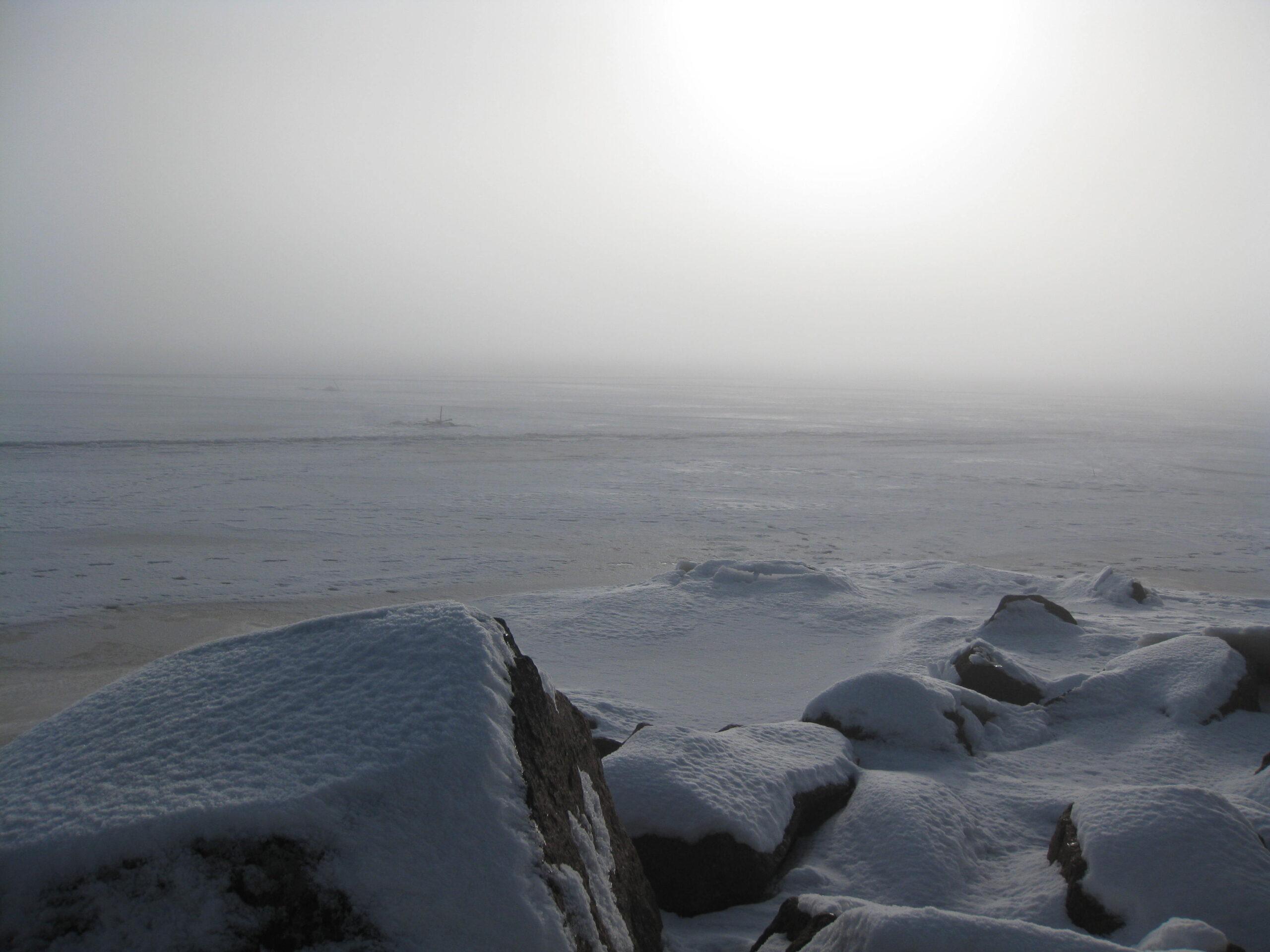 Jäinen meren selkä, lumipeitteisiä kiviä etualalla. Aurinko paistaa pakkasusvan takaa.