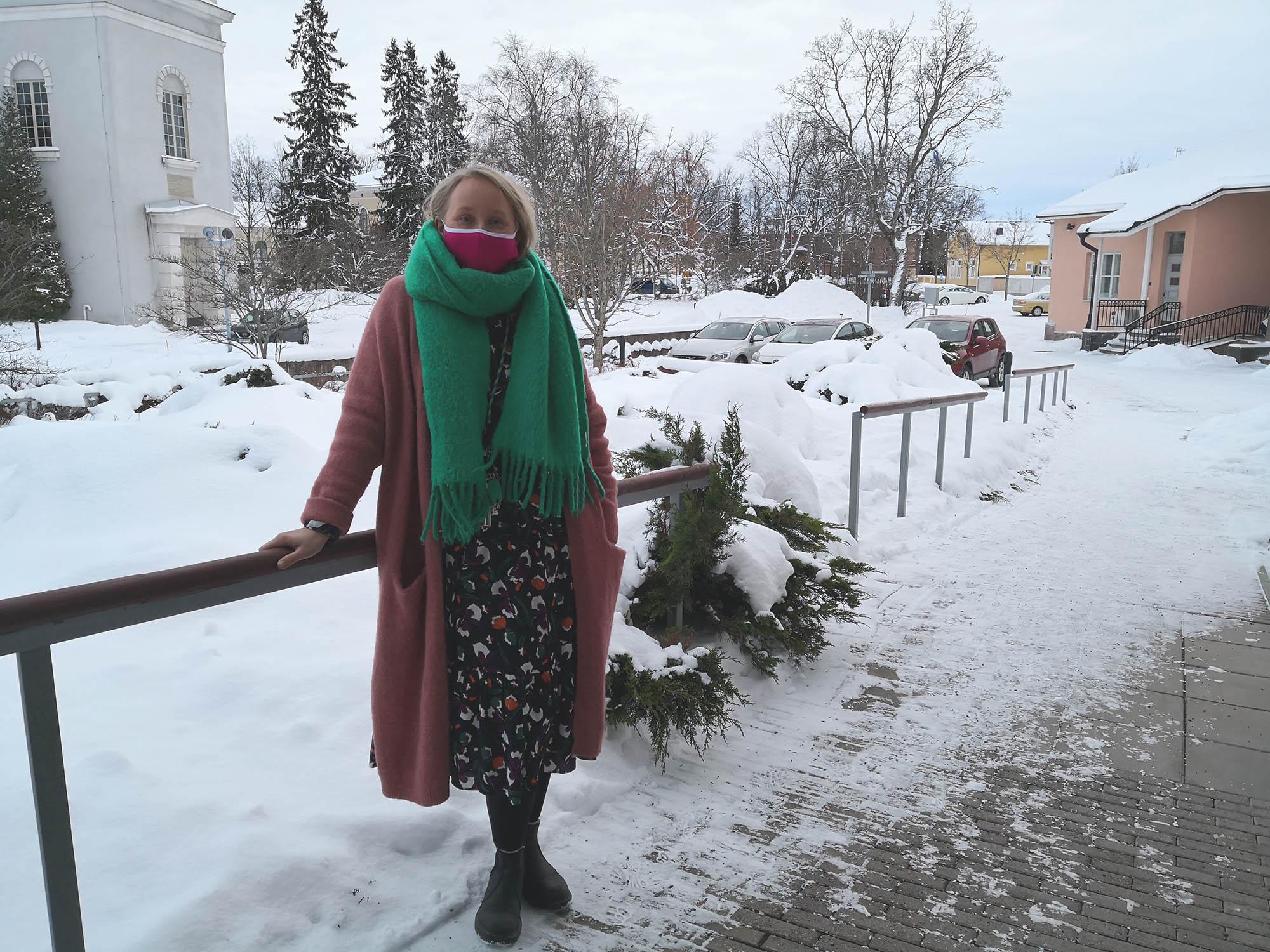 Kirkkoherra Anna Kinnunen maski kasvoillaan ulkona Marian kirkko taustalla