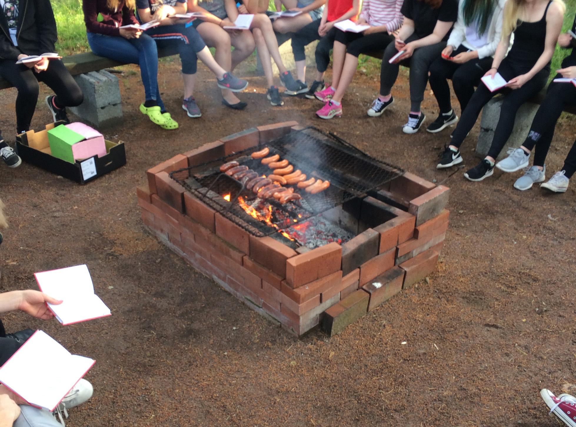 Makkarat paistuvat grillissä ympärillä lapsia istumassa penkillä