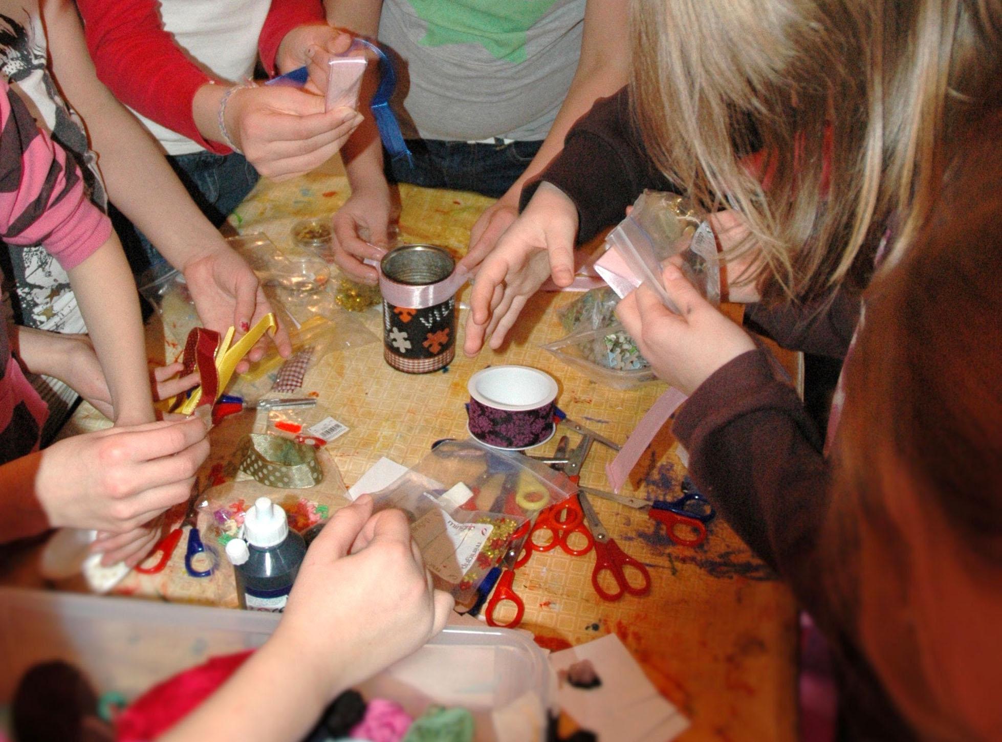 Lasten kädet tavoittelevat askartelutarvikkeita pöydällä