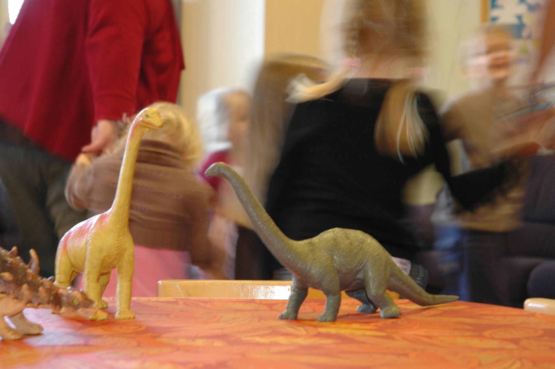 Dinosaurusleluja pöydällä, taustalla lapsia