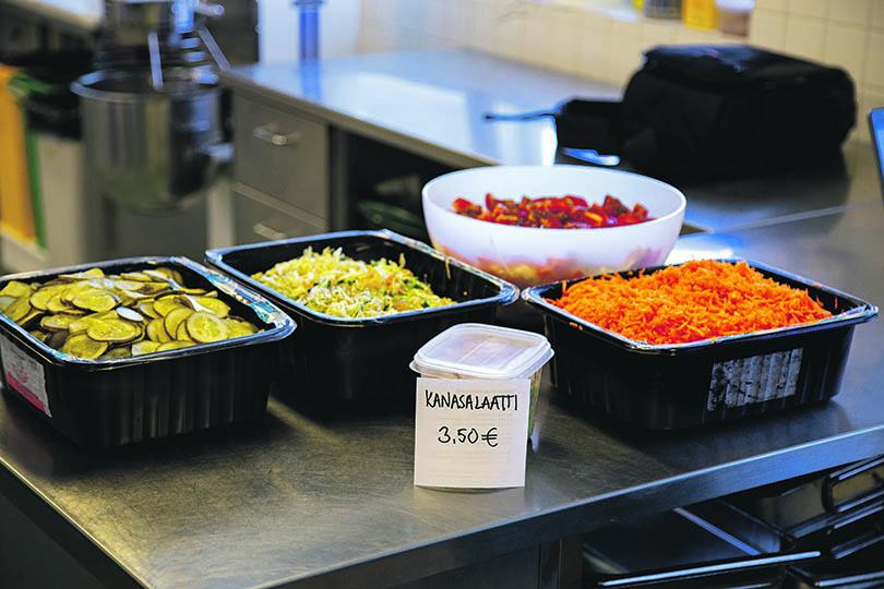 Suolakurkkuja, porkkanaraastetta ja muita salaatteja pöydällä
